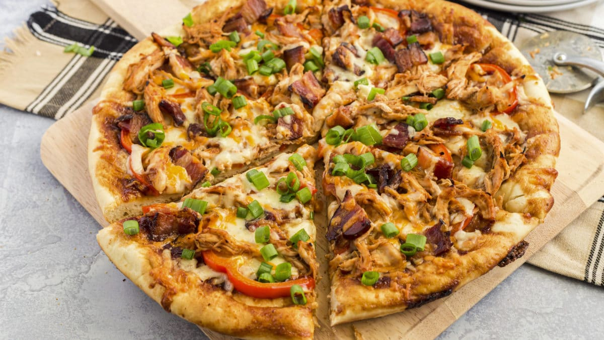 Cheesy bbq chicken pizza with green onions, bacon and chicken cooked in a handi foil pan