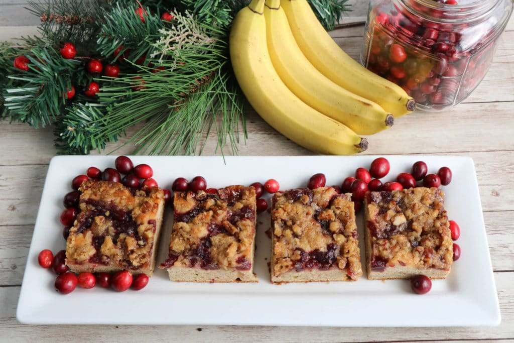 Banana Cranberry Coffee Cake cut in squares on a white plate
